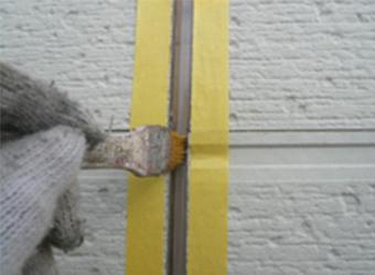 マスキングをしてプライマーと呼ばれる、コーキングが密着するためのものを塗布しています。