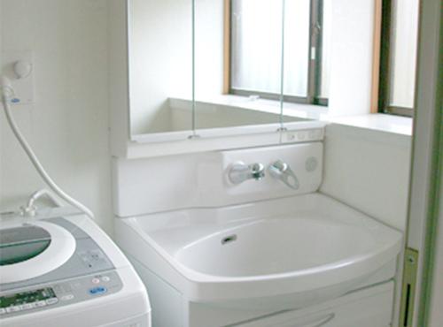 K様邸の洗面化粧台はタカラスタンダードのオンディーヌをご採用いただきました。三面鏡はミラー裏にたっぷりな収納スペースがあり、サイドのミラーは内側にも外側にも開く両開きです。また、光のあたり具合で豊かな表情を見せる、水平ラインを基調にした「ウィングカット」のホーロー扉は、美しいホーローに映える七宝引手を採用しています。