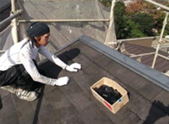 屋根に「タスペーサー」と呼ばれる密着防止材を挿入している様子です。これを入れないで塗装をすると、雨漏りの可能性が高まります。