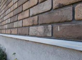 基礎と外壁の間にある土台水切りの下塗りの様子です。鉄部のため、ニッペのパーフェクトプライマーを使用しています。