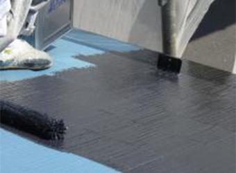 屋根の上塗りの様子です。ミズタニの快適サーモBio・ブラックを使用しています。
