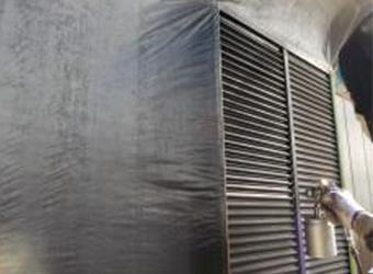 雨戸に下塗り材を吹き付けています。染めQ・ミッチャクロンを使用しています。